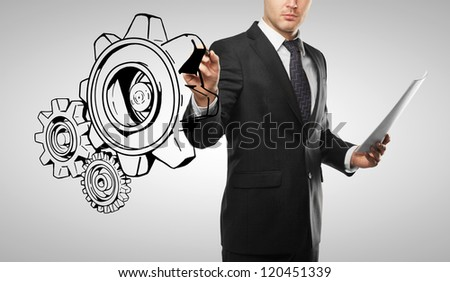 businessman drawing gears on white background - stock photo