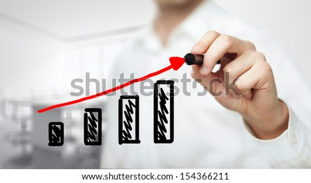 businessman drawing graph in office - stock photo