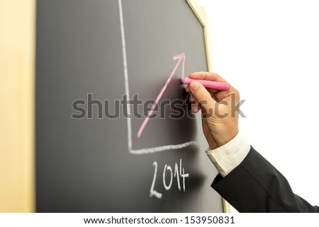 Businessman drawing growing financial graph for year 2014. - stock photo