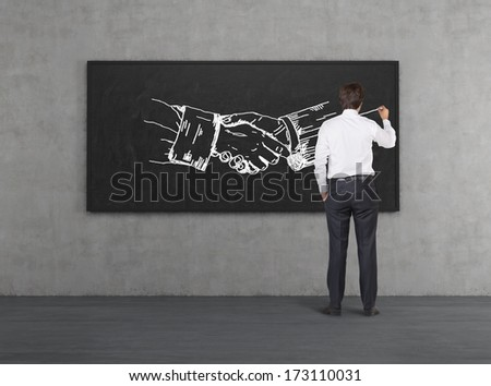 Businessman drawing handshake in a chalkboard - stock photo