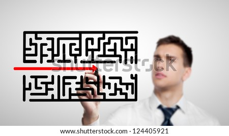 businessman drawing labyrinth on a white background - stock photo