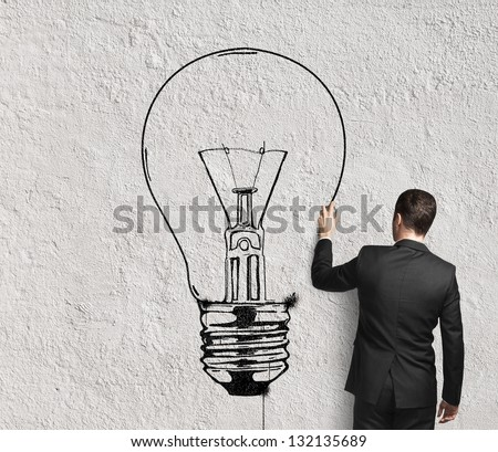 businessman drawing lamp on wall - stock photo