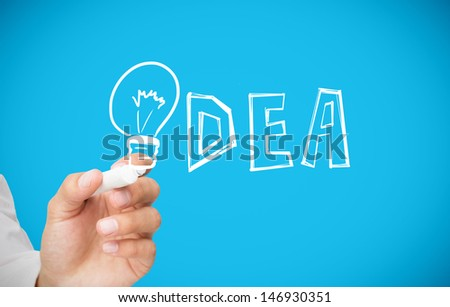 Businessman drawing light bulb as the i in idea on blue background
