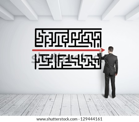 businessman drawing maze on white wall - stock photo