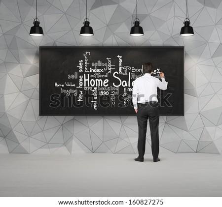 Businessman drawing on a blackboard - stock photo