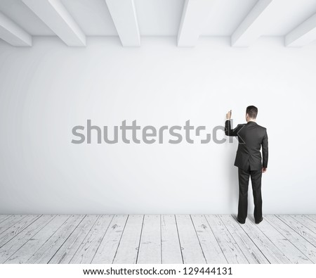 businessman drawing on white wall - stock photo