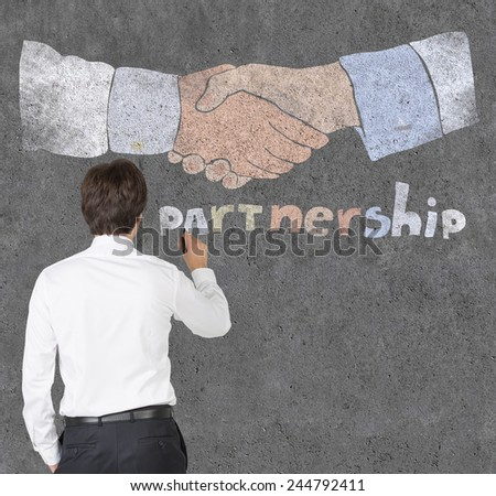 businessman drawing partnership symbol on a concrete wall - stock photo