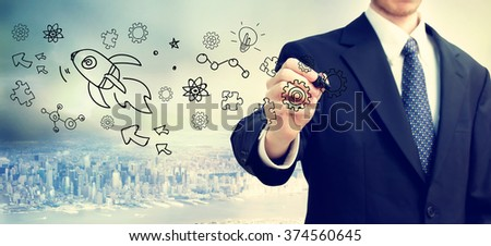 Businessman drawing Rocket and gears concept on blurred abstract background