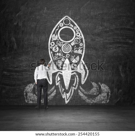 businessman drawing rocket with business icons on concrete wall - stock photo
