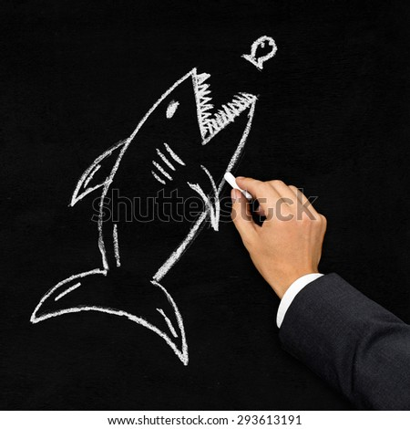 Businessman drawing shark hunting little fish with chalk on blackboard - acquisition, challenge or danger concept - stock photo