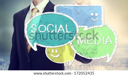 Businessman drawing Social Media colorful speech bubbles - stock photo