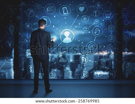 Businessman drawing social media connection scheme on glass window with night cityscape background  - stock photo