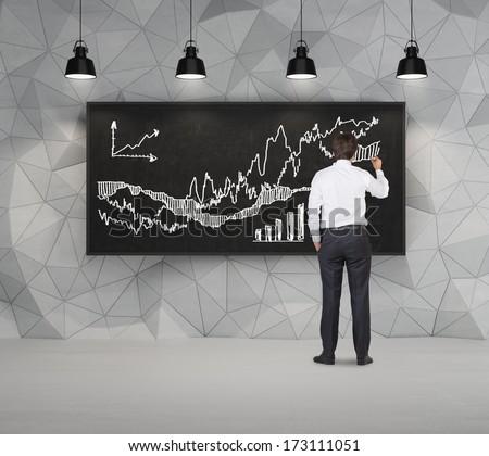 Businessman drawing stock graph - stock photo