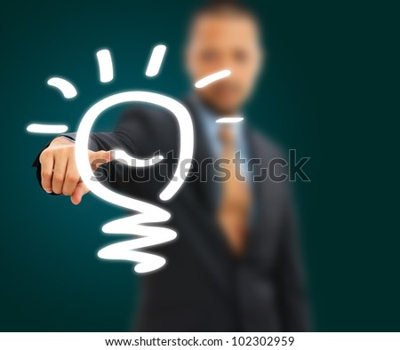 Businessman drawing the lightbulb by finger - stock photo