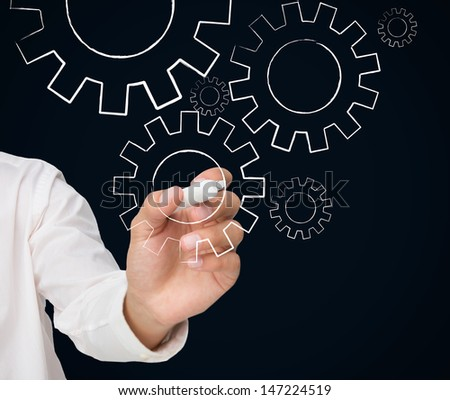 Businessman drawing white cogs and wheels on black background