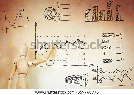Businessman draws various graphs. Abstract image with a wooden puppet - stock photo