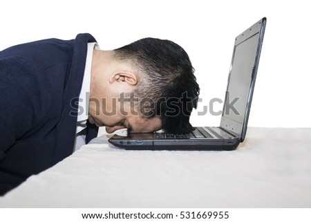 Businessman dreams while sleeping on laptop on white background