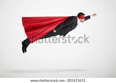 businessman dressed as a superhero in red mask and cloak flying up over light grey background - stock photo