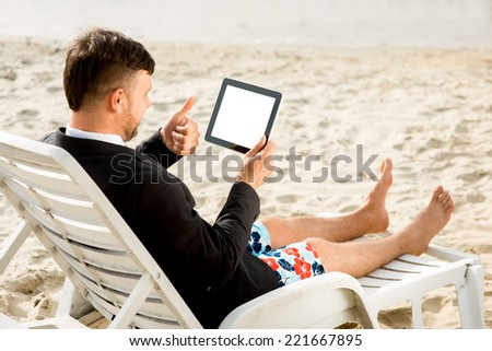 Businessman dressed in suit and shorts having video call with digital tablet on the sunbed at the beach - stock photo