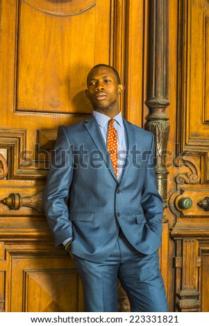 Businessman. Dressing formally in blue suit, patterned shirt and necktie, wearing ear stud, short haircut, a young guy is standing in the front of an old style office door, relaxing, thinking. - stock photo