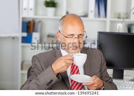 businessman drinking a cup of coffee in the office - stock photo