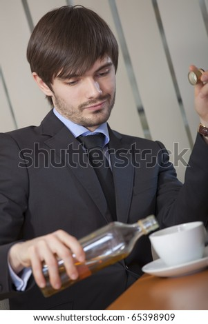 businessman drinking alcohol by the work in office