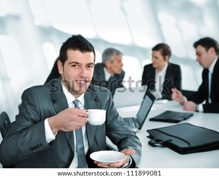 Businessman drinking coffee at meeting - stock photo