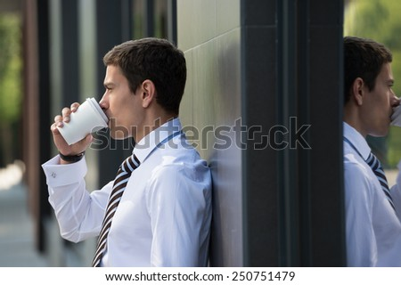 Businessman drinking coffee leaning on wall of modern office building. Urban professional smiling happy wearing white shirt holding disposable coffee cup. Handsome male model in his twenties. - stock photo