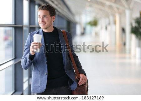 Businessman drinking coffee walking in airport. Casual urban professional smiling happy wearing suit jacket holding disposable coffee cup on travel. Handsome male model in his twenties. - stock photo