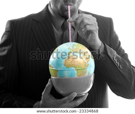 Businessman drinking the world, a power leader metaphor - stock photo