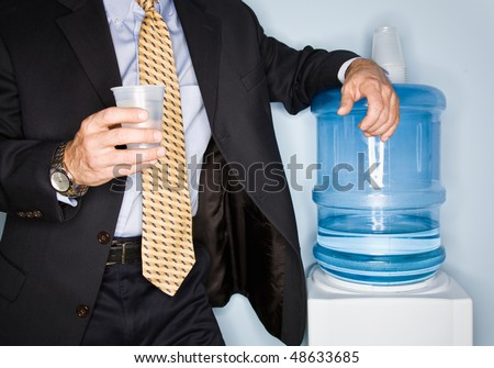 Businessman drinking water from water cooler - stock photo