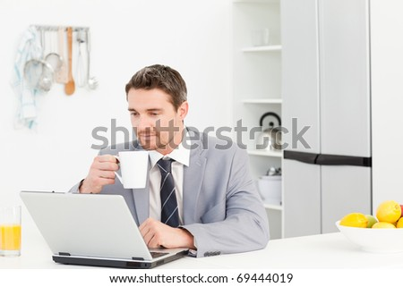 Businessman drinking while he is looking at his laptop at home - stock photo