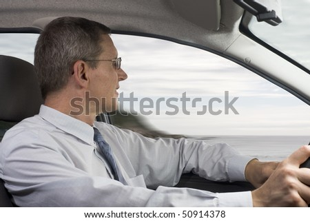 Businessman driving a car at the sea - stock photo