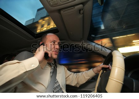 Businessman driving in car and talking on cell phone. - stock photo