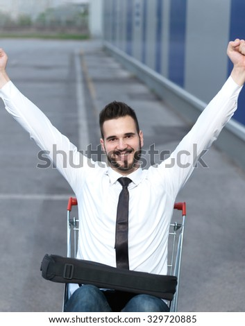 businessman driving in the shopping cart, consumerism