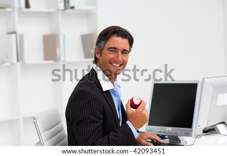Businessman eating a fruit at work and smiling at the camera - stock photo