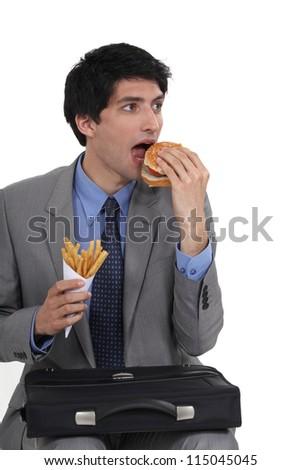 Businessman eating junk food - stock photo