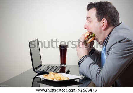 Businessman eating junk food while working - stock photo