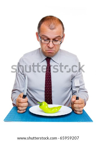 Businessman eating one green pepper isolated on white background