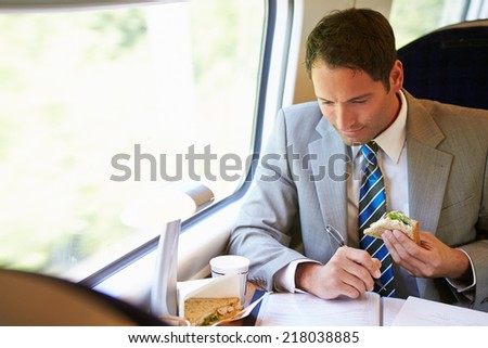 Businessman Eating Sandwich On Train Journey - stock photo