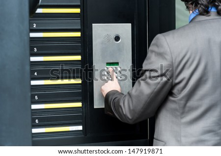 Businessman entering safe code to unlock the door - stock photo