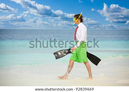 Businessman entering the ocean waters wearing snoring mask with flippers and wearing formal clothes with red tie entering water on the beach - stock photo