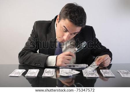 Businessman examining some banknotes through a magnifying glass - stock photo