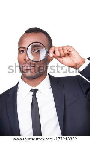 Businessman examining you. Serious young African man in formalwear looking through a magnifying glass while standing isolated on white background  - stock photo