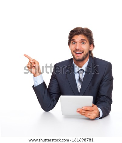 businessman excited smile point finger side empty copy space, using tablet pad computer, handsome young businessman sitting at the desk wear elegant suit, isolated over white background - stock photo