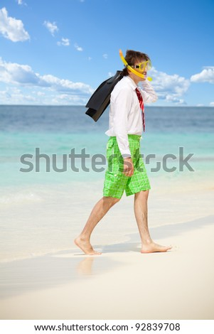 Businessman exiting the water wearing snoring mask with flippers and wearing formal clothes with red tie entering water on the beach - stock photo