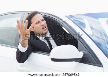 Businessman experiencing road rage in his car - stock photo