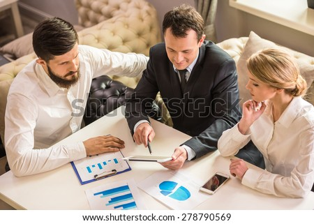 Businessman explaining a financial plan to colleagues at meeting. - stock photo