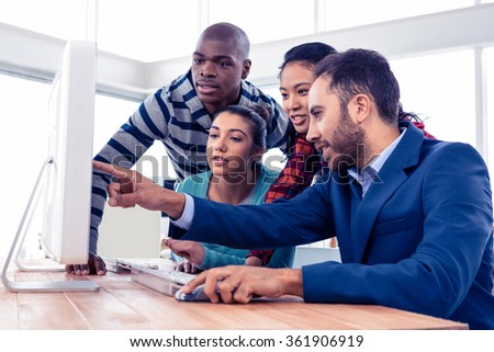 Businessman explaining colleagues over computer in creative office - stock photo