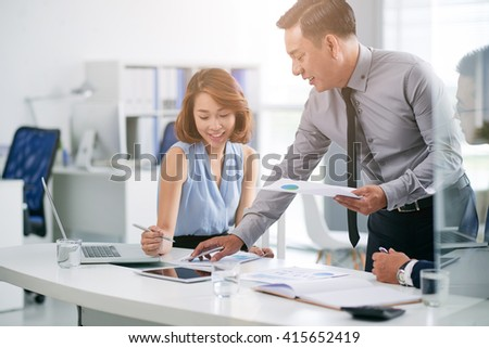 Businessman explaining data in document to his female colleague - stock photo